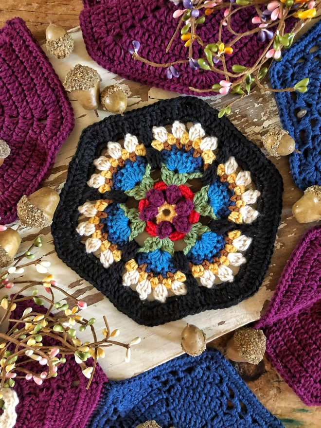 Frida's Flowers hexagon in black, red, purple, blue, white, and green.