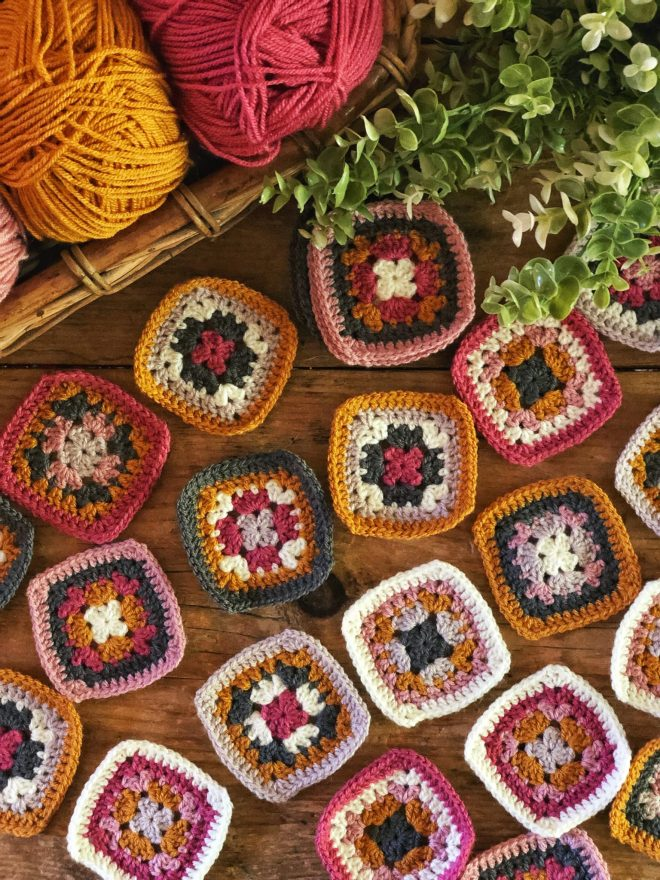 The Harmony Blanket granny squares in mustard, pink, white, and grey.