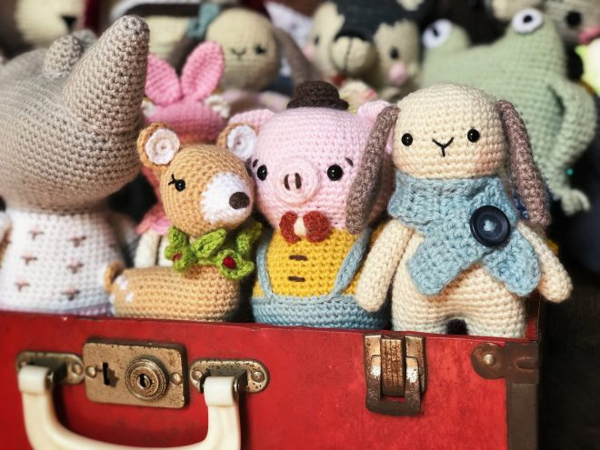 Close up of amigurumi animals in red suitcase. Close up of bunny and pig.