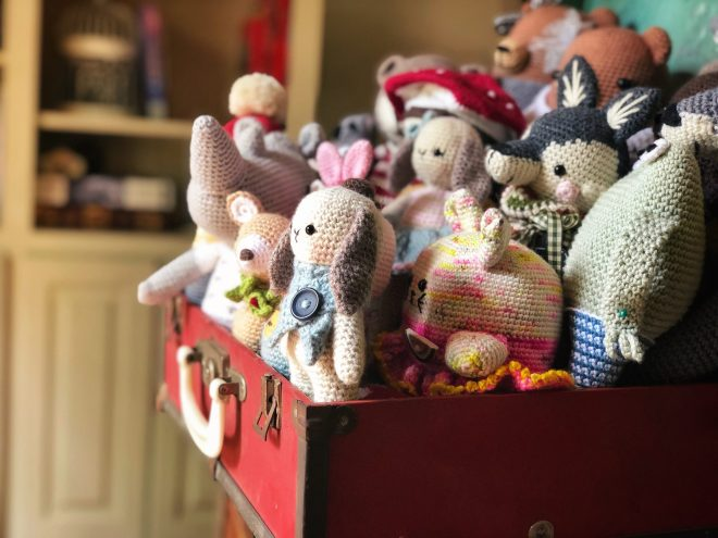 Side view of all the amigurumi animals in the red suitcase.