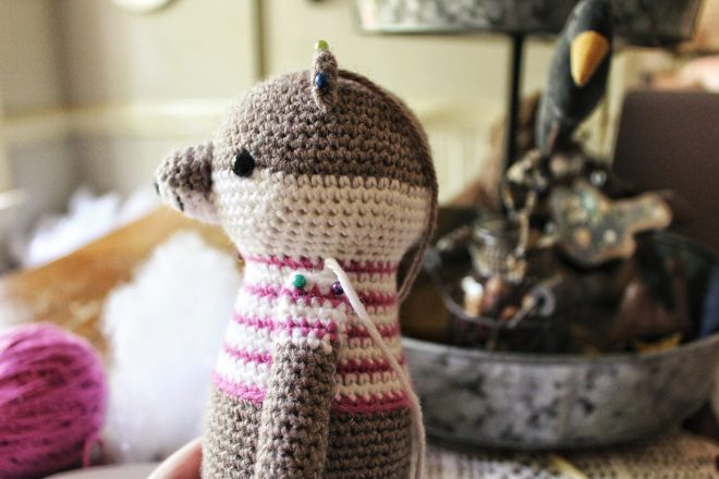 Side view of amigurumi otter with pinned ears and arms.