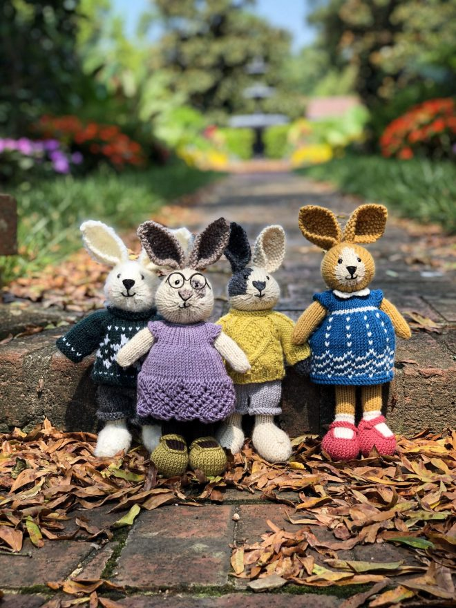 Knitted bunnies in clothes in a garden.