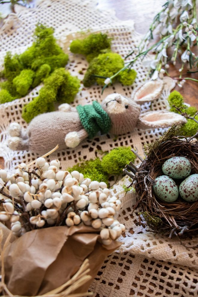Knitted bunny laying on a table with moss, a nest with bird eggs and lace.