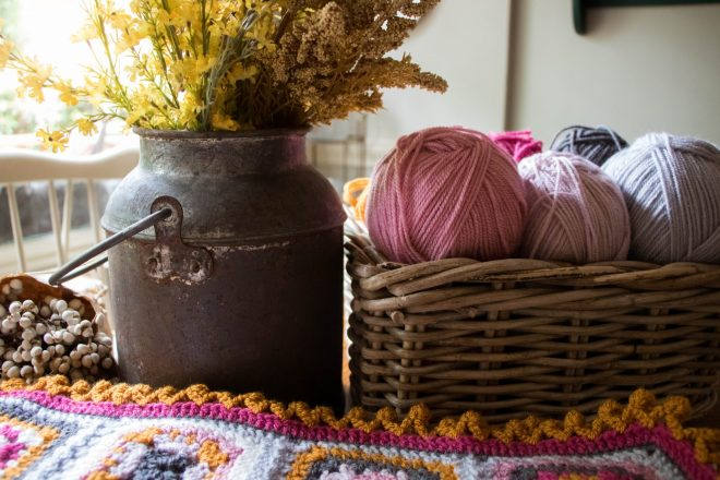 Basket of yarn beside a granny square blanket.