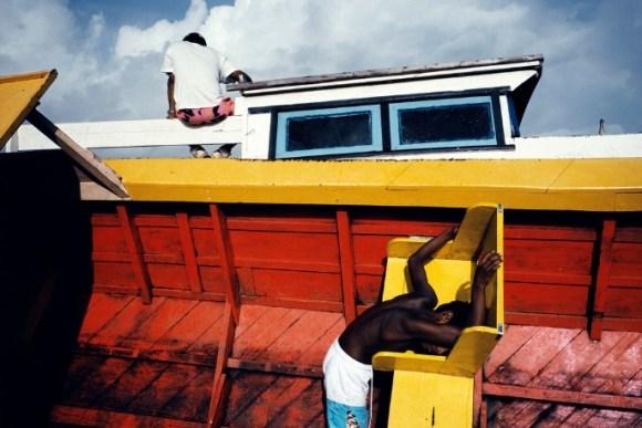 Deux enfants sont sur un bateau rouge et jaune
