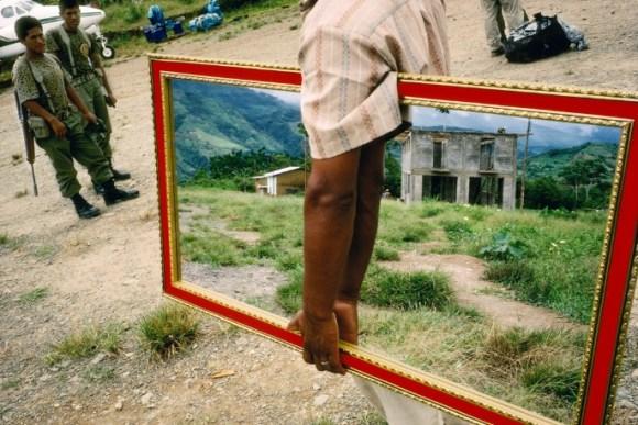 Un vendeur de miroir marche près de deux militaires