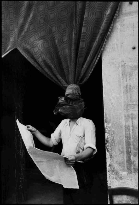 cartier-bresson : un rideau cache le visage d'un homme