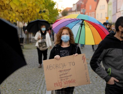 dziewczyna z tęczową parasolką trzyma transparent