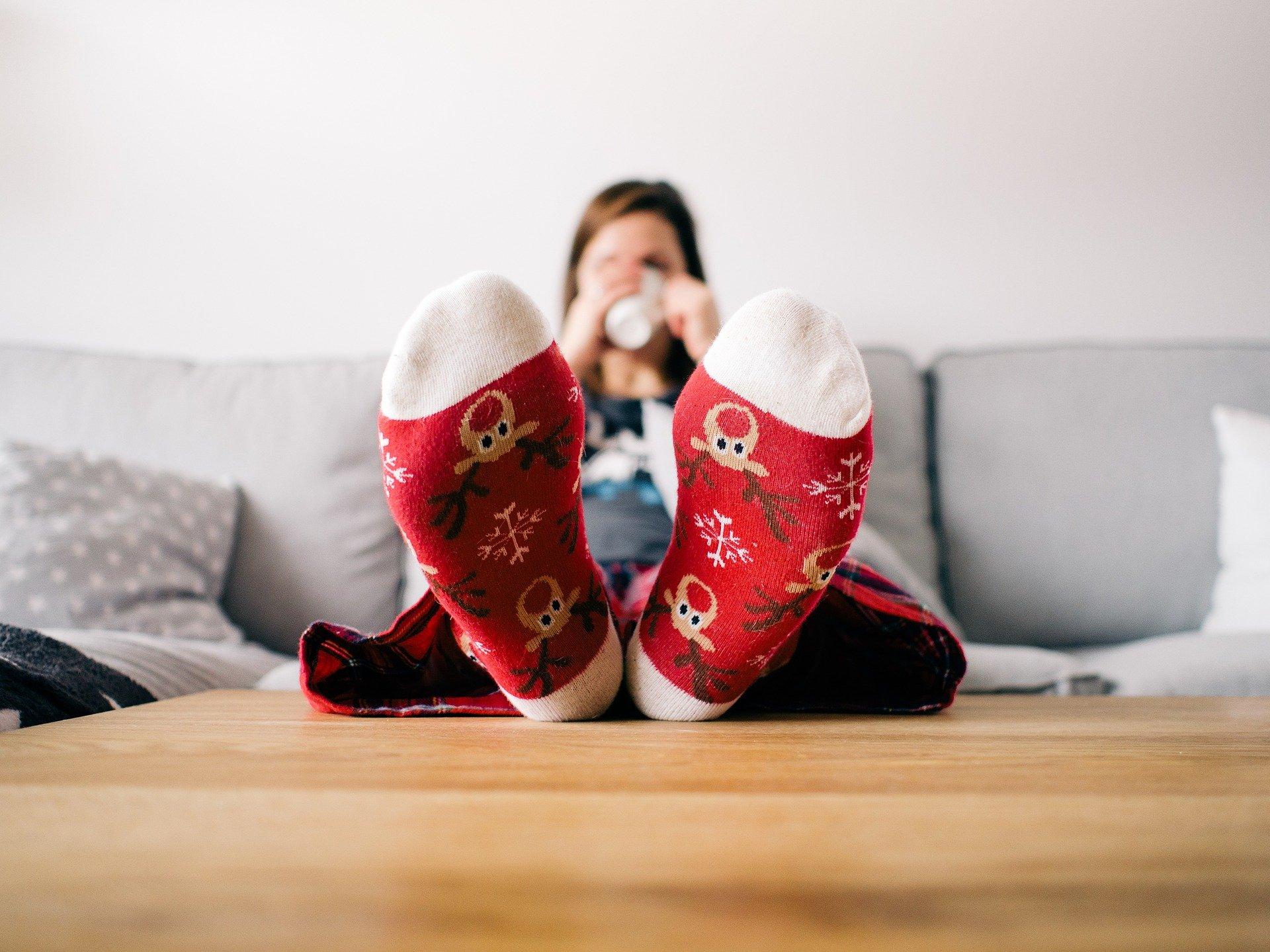 Ein Kind mit Weihnachtssocken sitzt auf dem Sofa und trinkt einen Kakao