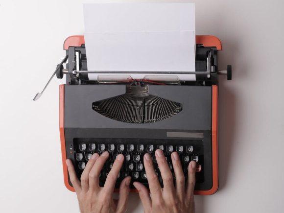 writer working on typewriter in office Materialgestütztes Schreiben oder Aufgabenart IV für ZP 10 oder Abitur sind gut umzusetzen.