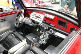 The inside of an original Austin Mini, with add-ons, including a  PSOne.