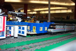 A lego train cruises along a straight run of track.