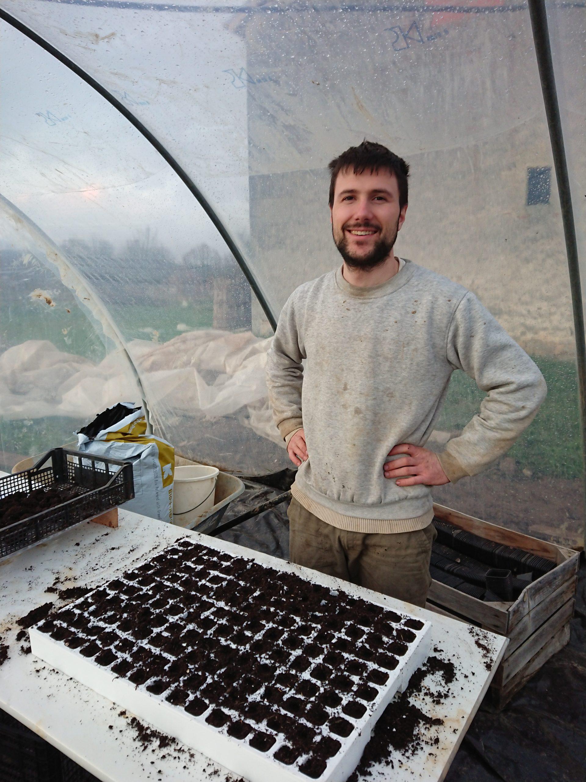 Benjamin sourit devant une plaque de semis dans sa serre à plants