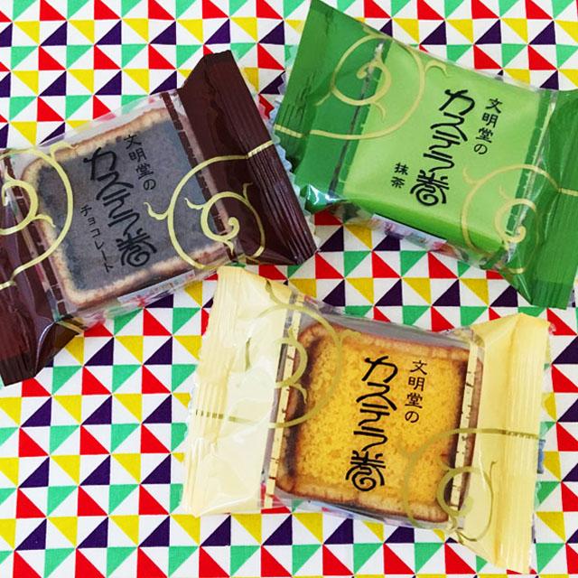 文明堂神戸店のプレーン、チョコ、抹茶の3種類のカステラ巻が並べられている,