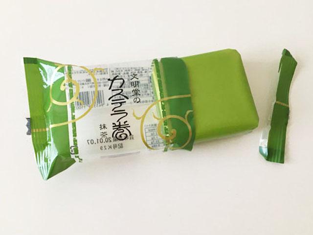 文明堂神戸の個包装された抹茶味のカステラ巻を開封しようとしている様子,