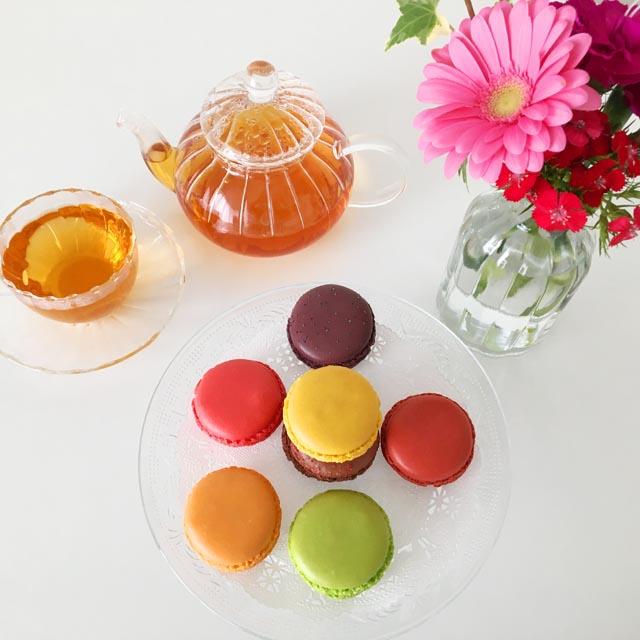 ダロワイヨの7種類のマカロンと紅茶と花瓶に花が飾られている