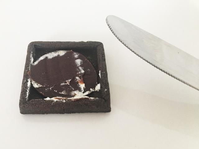プレスバターサンド,バターサンド〈黒〉にサンドされているチョコレートキャラメルをナイフで とろうとしている様子,