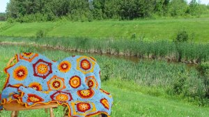 """Photo of """"Sunrise"""" Afghan, by Les Becker, draped over a chair with Fort Creek in the background"""