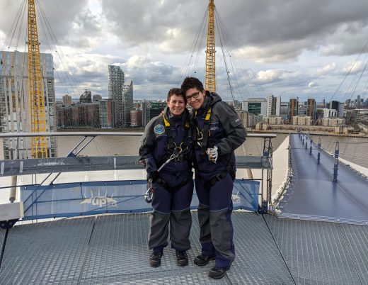 Picture of Sharon and I standing at the top of The O2 after our climb. A London Skyline sits behind us. We are dressed in climbing gear and have climbing equipment attached to us,