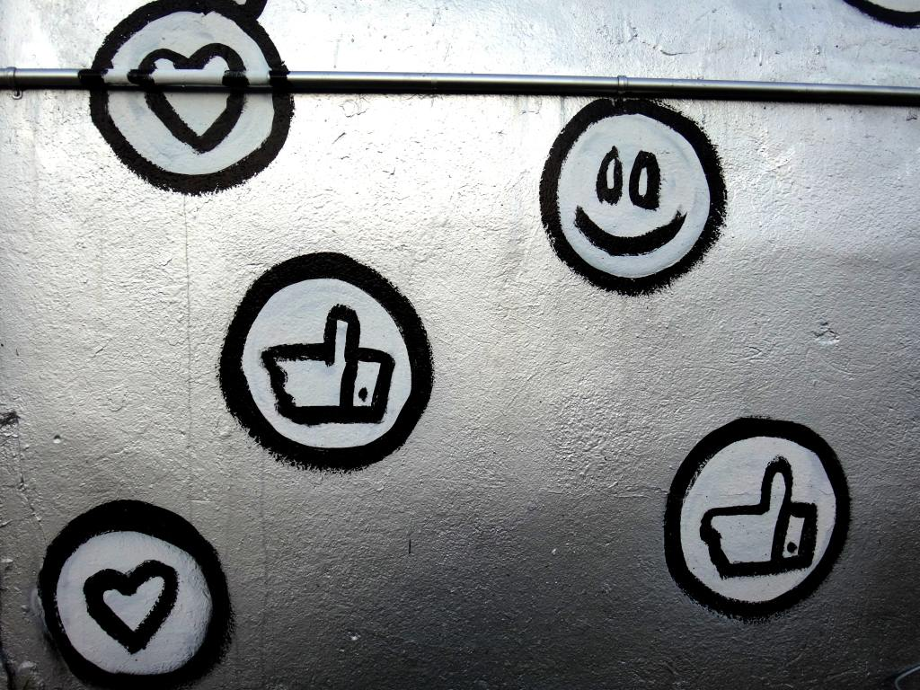 Photo of a metallic wall with a number of spray painted smiley faces and thumbs up.