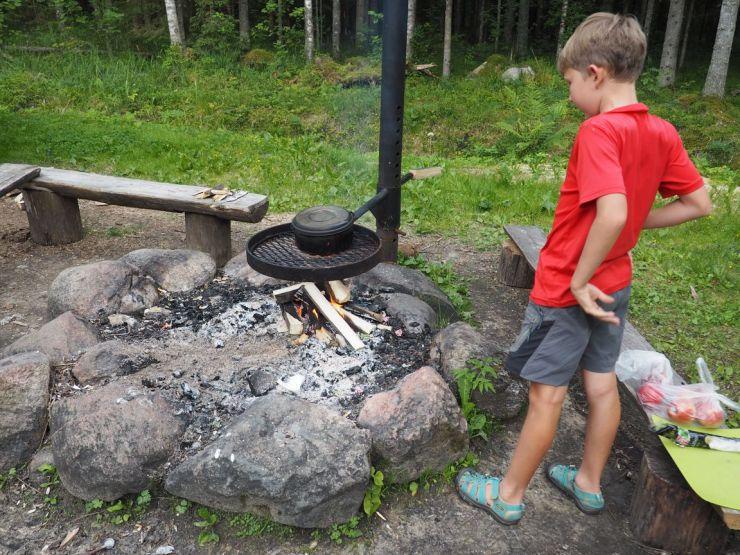 Après avoir coupé les buches, Joseph s'assure que le feu prend bien.
