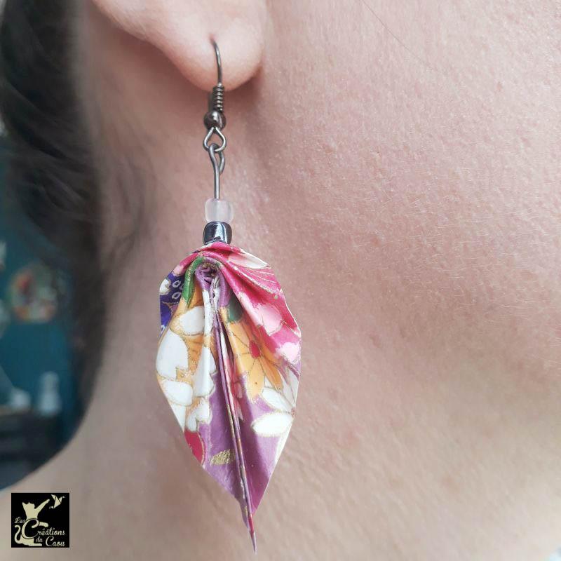 Boucles d'oreilles en origami. Le pliage est une palme réalisée à partir d'un papier japonais fuchsia au motif fleuri coloré.