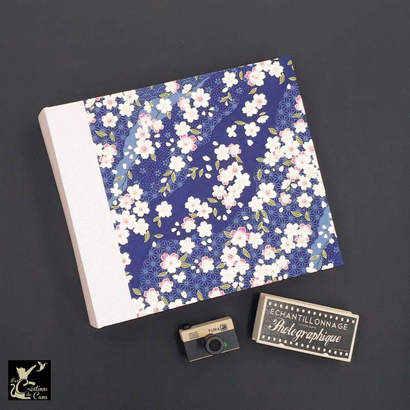 Album photos artisanal permettant d'accueillir 100 photos. Il est recouvert d'un élégant papier japonais marine et rose poudré.
