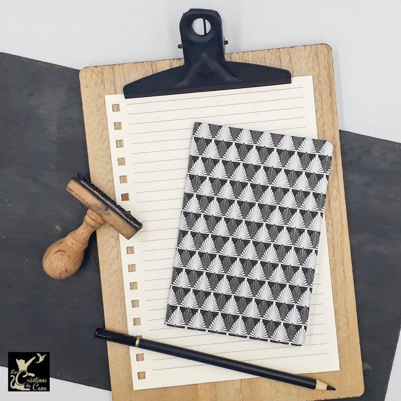 Carnet de notes au format très pratique A6. La couverture est recouverte à la main d'un papier indien noir orné de motifs géométriques blancs et anthracite.