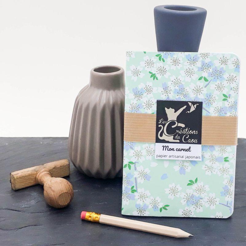Carnet de notes au format A6. La couverture est recouverte à la main d'un papier japonais au fond vert d'eau orné de fleurs de sakura.