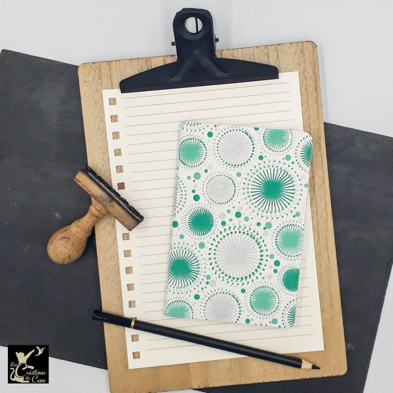 Carnet de notes au format A6. La couverture est recouverte à la main d'un papier indien blanc orné de motifs géométriques blancs, argentés et turquoise.