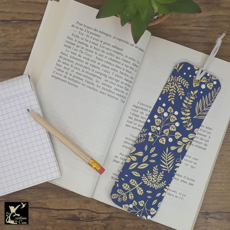 Ne perdez plus le fil de vos lectures ! Ce marque-page artisanal, recouvert d'un élégant papier japonais bleu foncé orné de végétaux dorés deviendra votre allié.
