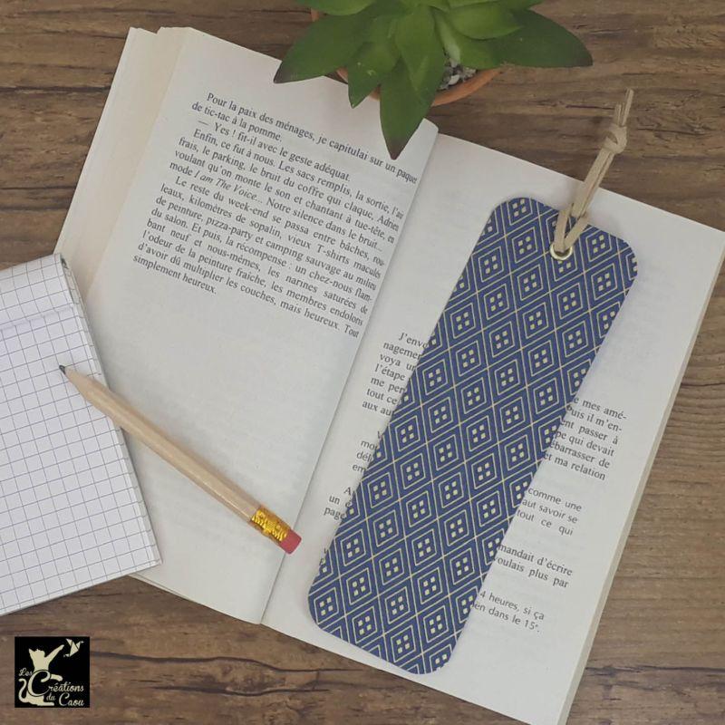 Ne perdez plus le fil de vos lectures ! Ce marque-page artisanal, recouvert d'un élégant papier japonais bleu foncé orné de losanges dorés deviendra votre allié.