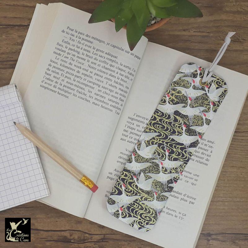 Ne perdez plus le fil de vos lectures ! Ce marque-page artisanal, recouvert d'un élégant papier japonais orné de grues sur fond bleu nuit deviendra votre allié.