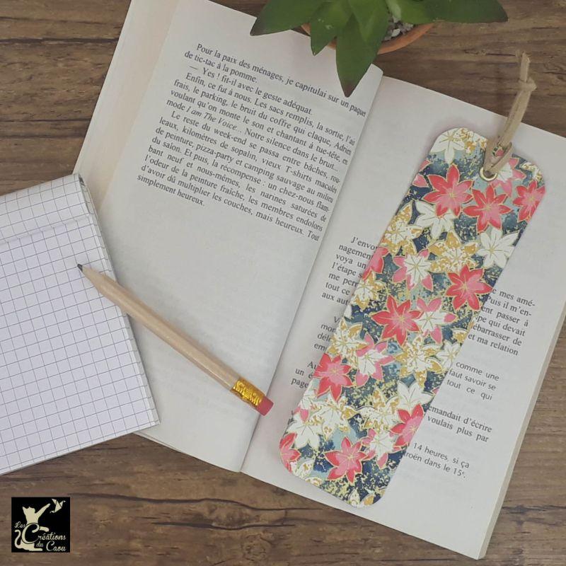 Ne perdez plus le fil de vos lectures ! Ce marque-page artisanal, recouvert d'un élégant papier japonais orné de feuilles aux tons moutarde, roses et blanches sur un fond bleu ciel à bleu turquoisedeviendra votre allié.