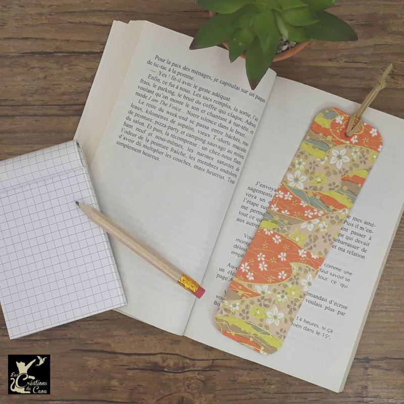 Ne perdez plus le fil de vos lectures ! Ce marque-page artisanal, recouvert d'un élégant papier japonais orné de fleurs sur fond orange, jaune, beige et gris clairdeviendra votre allié.