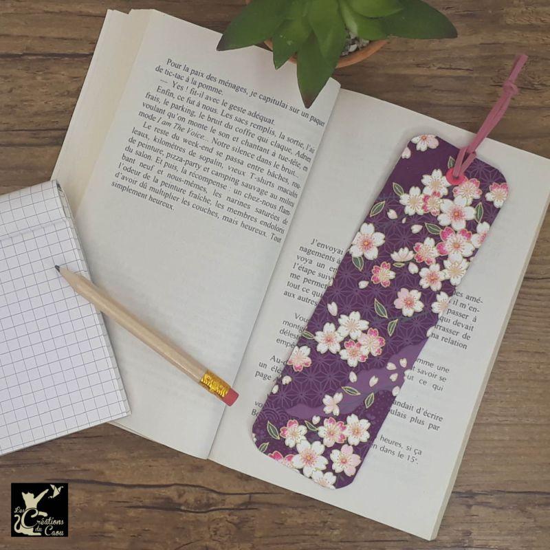 Ne perdez plus le fil de vos lectures ! Ce marque-page artisanal, recouvert d'un élégant papier japonais violet fleuri deviendra votre allié.