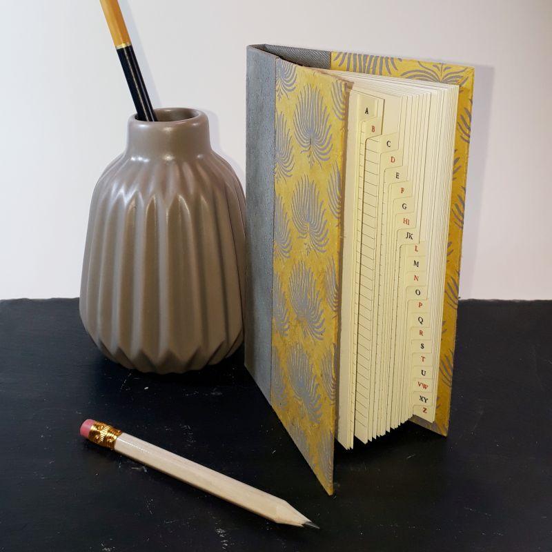 Petit répertoire de sac à main, dos carré collé, papier artisanal népalais moutarde, palmes anthracite.