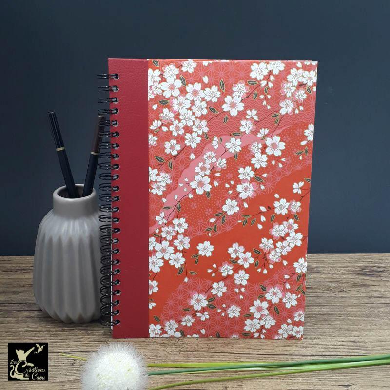 Répertoire à spirale recouvert d'un papier artisanal au motif de sakura sur fond rouge.