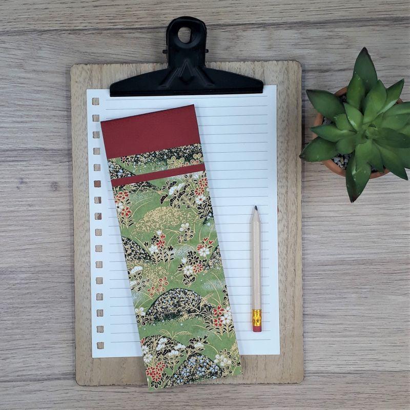 Bloc à listes réalisé à la main dans notre atelier de Lambersart (Lille), recouvert de papier japonais vert olive orné de motifs végétaux et de collines.