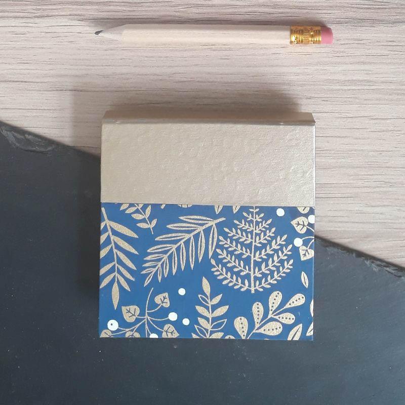 Porte bloc à post-it de la marque de papeterie lilloise : les créations du caou. Papier japonais bleu foncé, motifs de végétaux dorés.