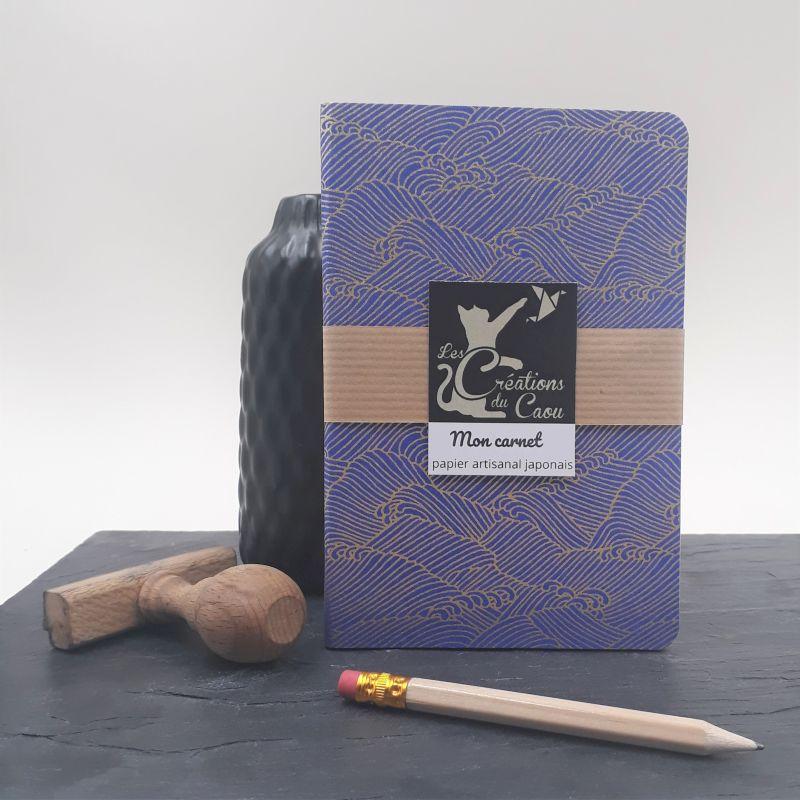 Carnet de notes au format A6. La couverture est recouverte à la main d'un papier japonais bleu roi au motif de vagues dorées..