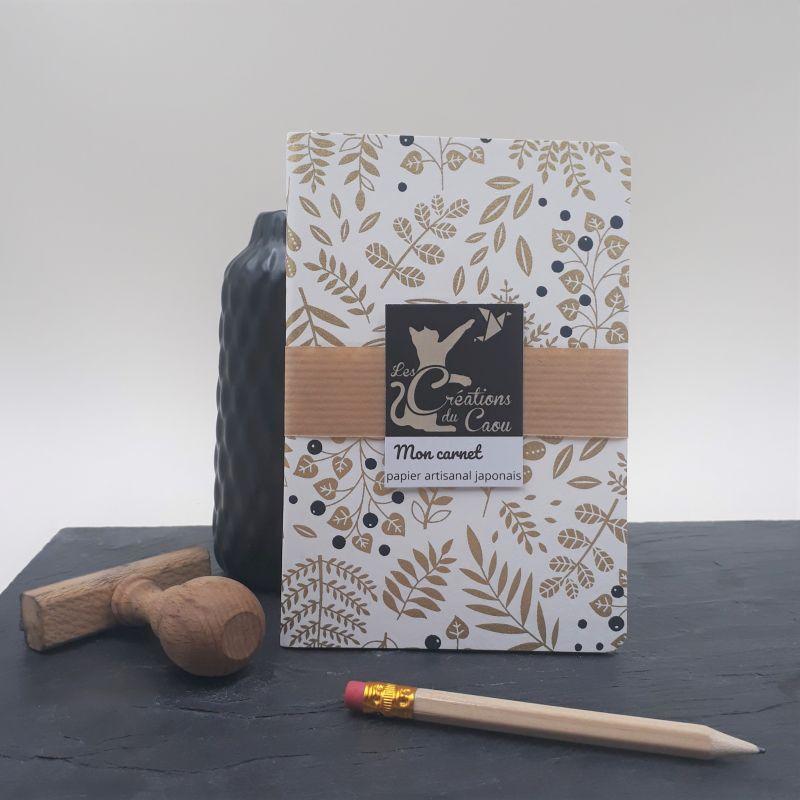 Carnet de notes au format A6. La couverture est recouverte à la main d'un papier japonais écru au motif de végétaux dorés et baies noires.