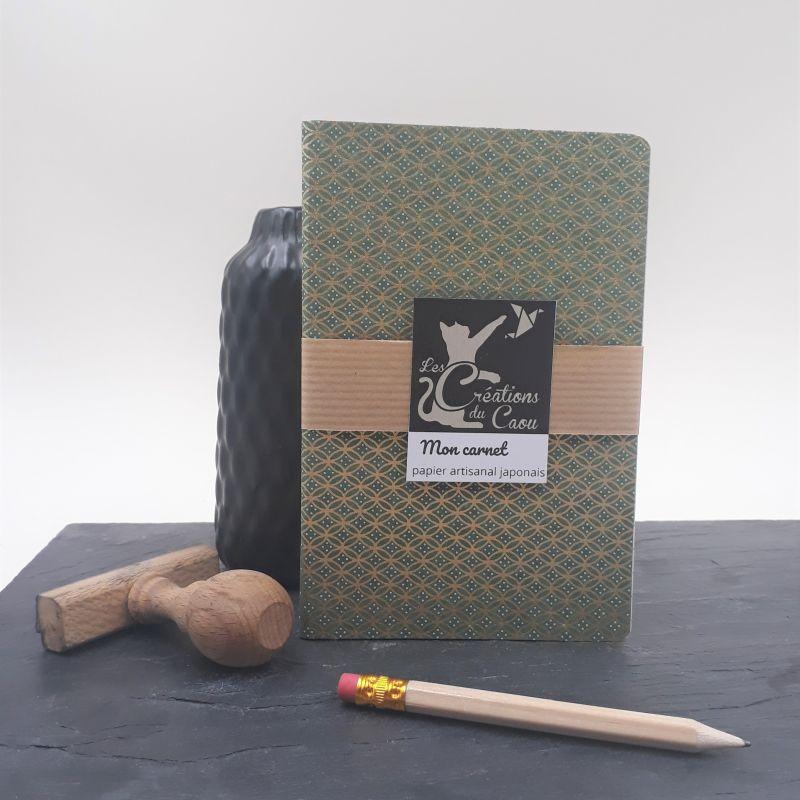 Carnet de notes au format A6. La couverture est recouverte à la main d'un papier japonais vert olive foncé au motif géométrique doré.