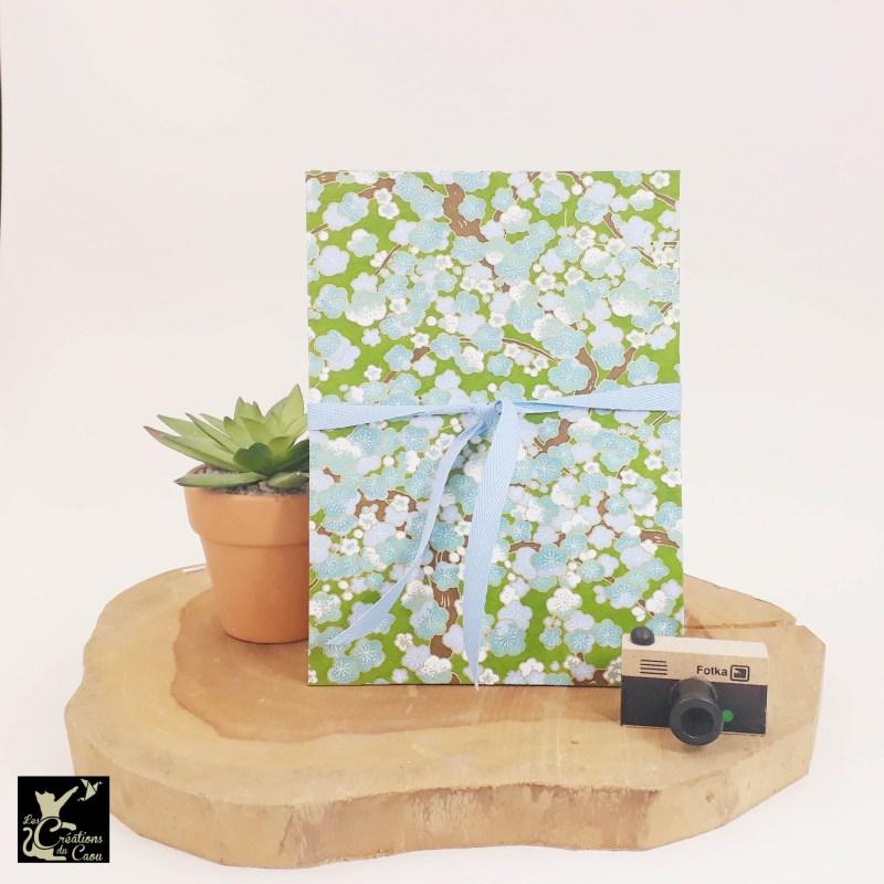 Album photo leporello réalisé à la main dans notre atelier de Lambersart (Lille), recouvert d'un papier japonais vert printemps au motif de fleurs de prunier blanches et bleues.