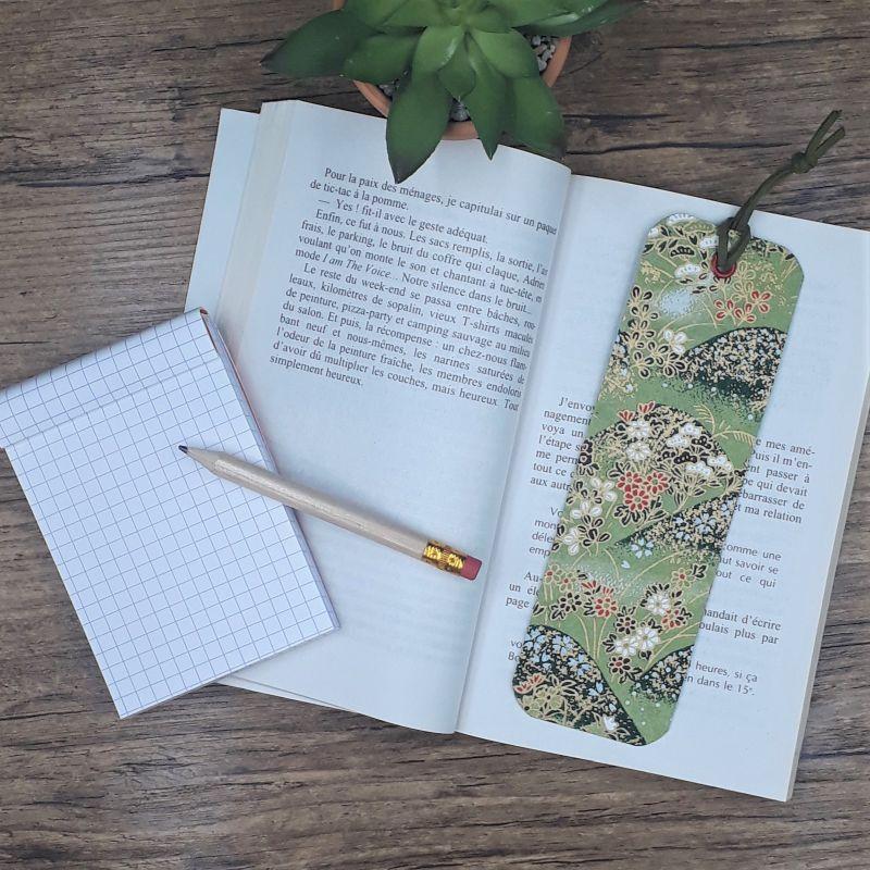 Marque-page artisanal réalisé entièrement à la main dans notre atelier de Lambersart (Lille) avec un élégant papier japonais vert olive au motif de collines fleuries.
