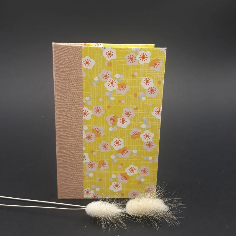 Répertoire de poche réalisé artisanalement recouvert d'un papier japonais jaune fleuri.