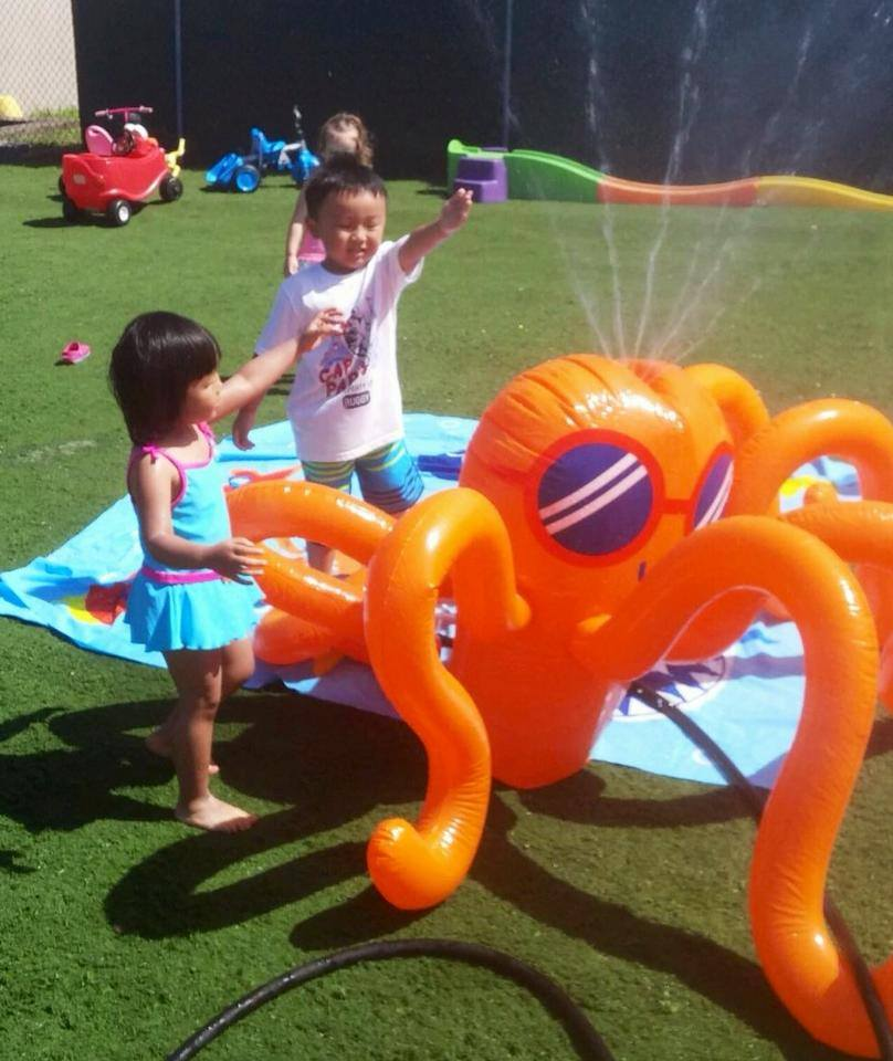 kids playing by sprinkler