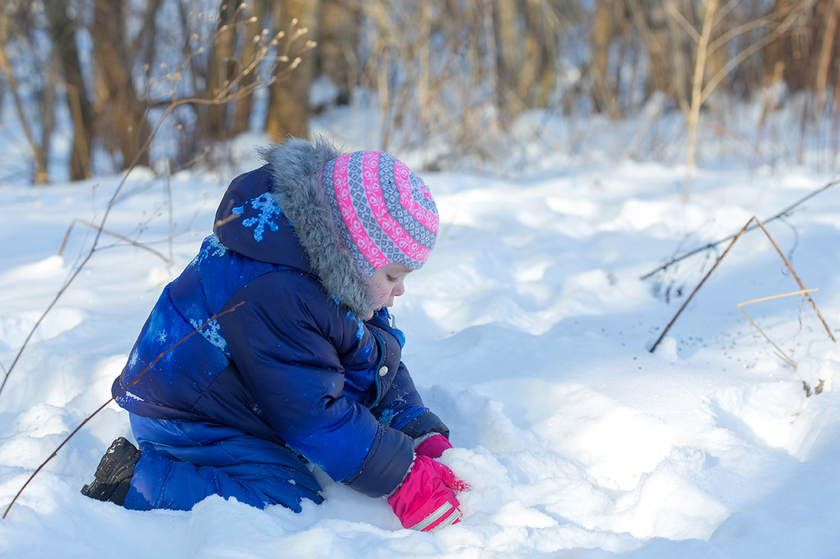 small child playing in snow