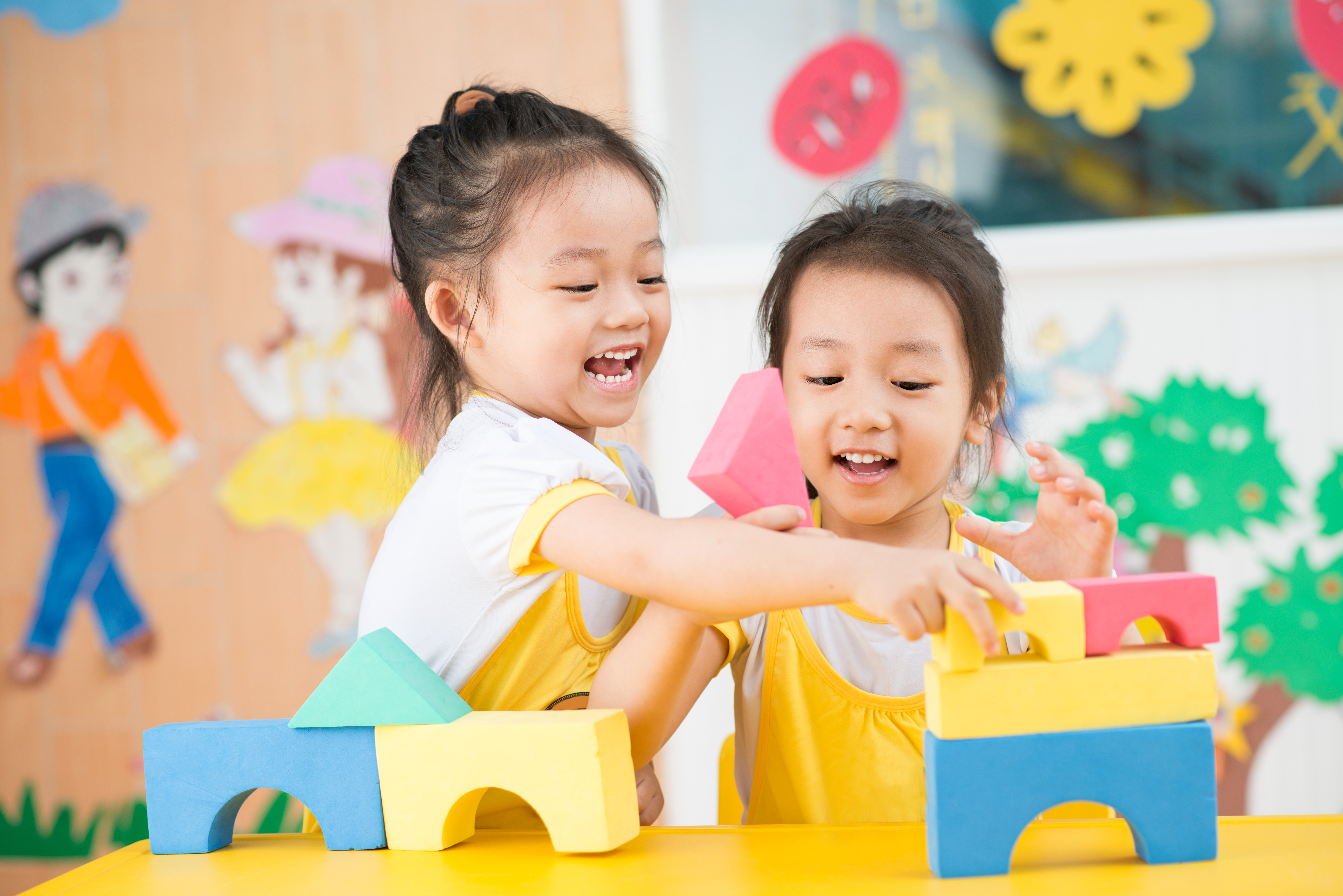 two little girls playing with blocks
