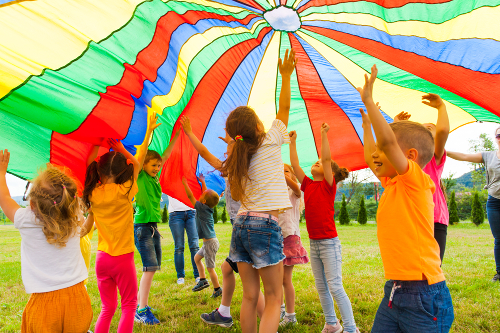 classmates playing together outside with parachute